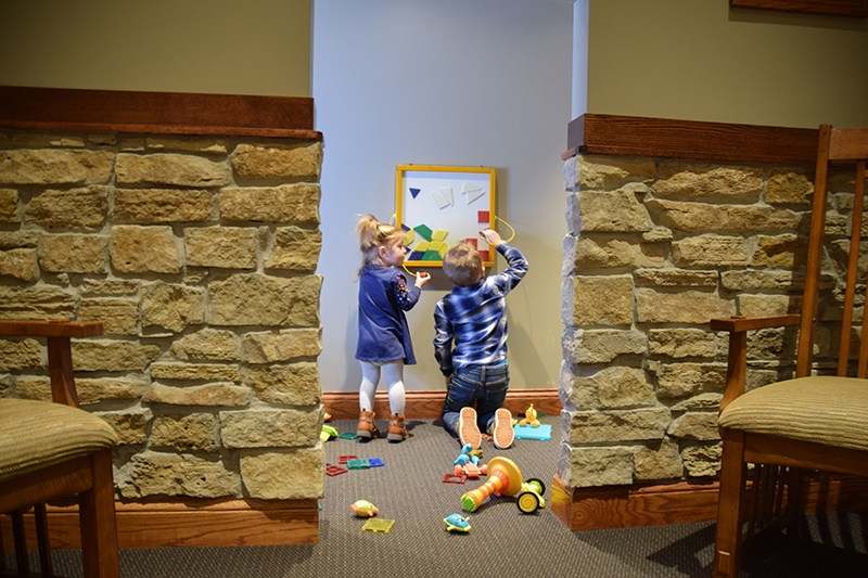 front office play area for kids with toys and two children playing