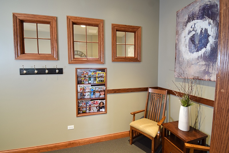 front desk waiting area with chairs, painting, windows, coat rack and reading material