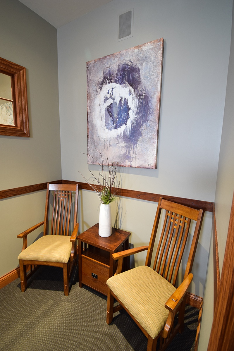 front office seating area with two chairs and modern art painting